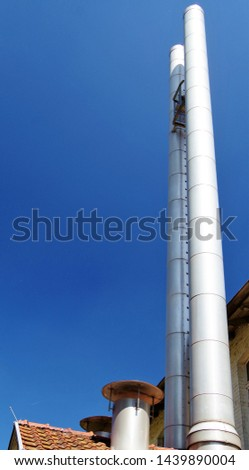 modern double-loft factory chimney looms in the blue sky,  #1439890004
