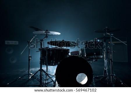 Modern drum set shot in smoky dark studio
