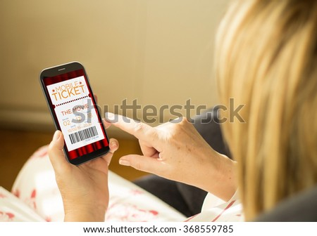 modern e-commerce concept: mature woman with 3d generated touchscreen smartphone with cinema tickets on the screen. Screen graphics are made up. #368559785