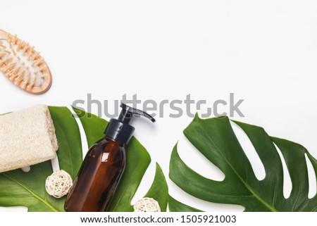 Modern eco bathroom essentials. Reusable dispenser, wooden hair brush and natural sponge lying on monstera leaves