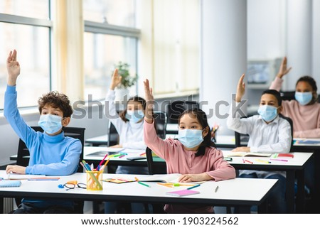 Modern Education And Pandemic Concept. Group of multicultural small pupils raising hands, sitting at desk in classroom, ready to answer a question. Schoolchildren wearing disposable medical face masks Photo stock ©