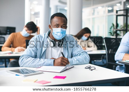 Modern Education During Pandemic Concept. Portrait of african american male student sitting at desk in classroom at university, wearing protective medical mask, writing in notebook, looking at camera