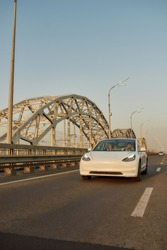Modern electric car driving along aspalted city road across bridge, vertical shot. Luxury and success concept