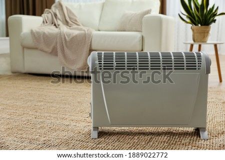 Modern electric convection heater on floor at home. Space for text