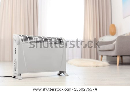 Modern electric heater on floor at home. Space for text