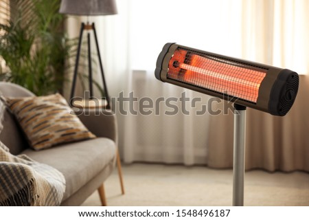 Modern electric infrared heater at home. Space for text