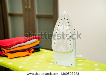 Modern electric iron and pile of clothes on ironing board #1360507928