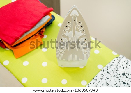 Modern electric iron and pile of clothes on ironing board #1360507943