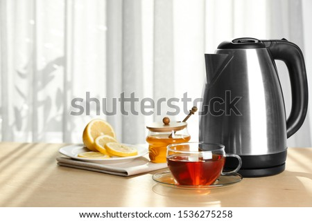 Modern electric kettle and cup of tea on wooden table indoors. Space for text Stock photo ©
