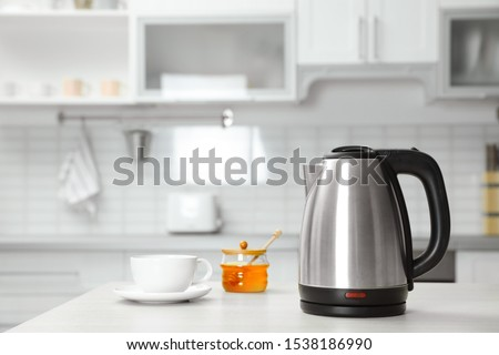 Modern electric kettle, cup and honey on wooden table in kitchen Stock photo ©