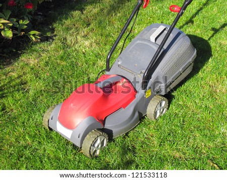 Modern electric lawn mower on the unmown lawn