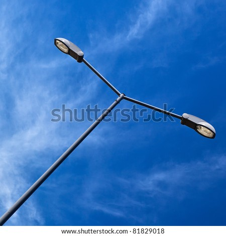 Modern electric street light pole over blue sky with clouds.