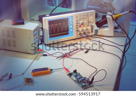 Modern electronic equipment in computer service center, oscilloscope and power pack connected to microchip. This image is toned #594513917