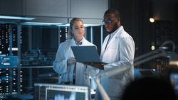 Modern Electronics Research, Development Facility: Engineer and Scientist Standing In High-Tech Laboratory, Use Laptop Computer, Talk, Design Silicon Microchips, Semiconductors, Manufacture Computers