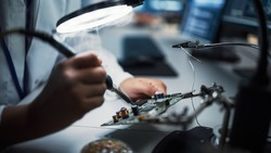 Modern Electronics Research, Development Facility: Female Engineer Does Computer Motherboard Soldering. Scientists Design PCB, Silicon Microchips, Semiconductors. Close-up Shot with Focus on Hands
