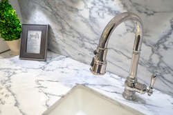 modern elegant  silver chrome Kitchen Faucet With Pull Down Sprayer all in one with small plant and frame on marble counter top