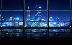 Modern empty and clean office interior with glass windows , Perth city skyline background , night scene .