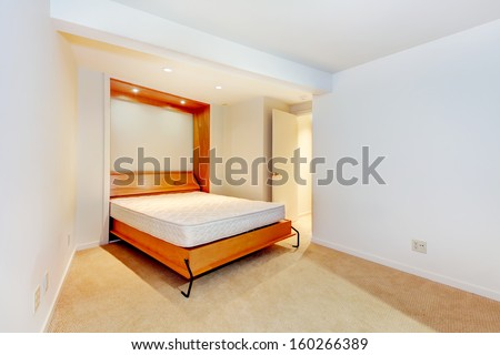 Modern empty bedroom with build in day bed and wood frame. Beige carpet. Luxury home interior, guest bedroom.