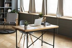 Modern empty wooden table with laptop and green plant on. Loft home workplace of freelancer or designer. Renovated stylish office workspace of businessman in apartment or flat. No people around.