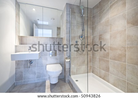 Modern en suite bathroom with large shower, toilet and wash basin in beige natural with natural stone tiled walls
