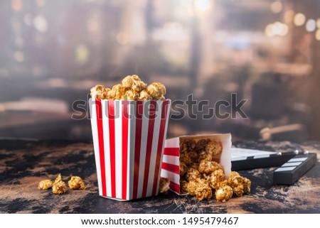 Modern entertainment background - homemade caramel popcorn and cinema clapper board
