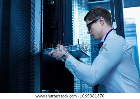 Modern equipment. Serious professional operator working with server equipment in the office Foto stock ©