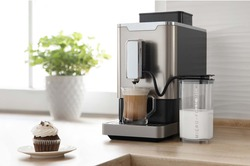 Modern espresso coffee machine in the kitchen makes cappuccino with milk container and cupcake on the table