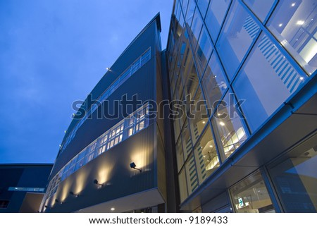 modern exterior  abstract architectural background with wall and window illumination and blue sky