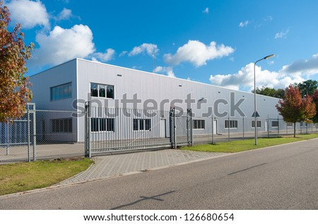 modern exterior of an industrial building, surrounded by a fence with iron gate #126680654