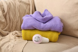 Modern fabric shaver and clothes on sofa