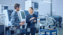 Modern Factory: Female Project Manager and Male Engineer Standing, Talking, Using Digital Tablet for Programming and Monitoring Assembly Line. Industry 4.0 Facility with High-Tech CNC Machinery