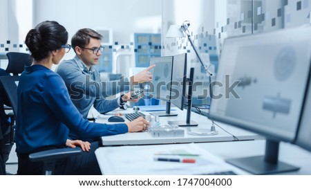 Modern Factory: Male Industrial Engineer Explains to Female Project Supervisor Functions of the Machine Part Comparing it to one on Computer Screen. They use CAD Software for Design, Development