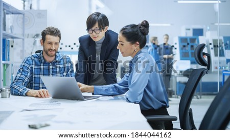 Modern Factory Office Meeting: Female Project Manager, Asian Branch Supervisor Talk with Chief Product Engineer who Shows Them Laptop Screen. Team of Professionals Solving Technological Problems Foto d'archivio ©