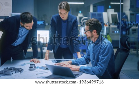 Modern Factory Office Meeting Room: Diverse Team of Engineers, Managers Talking at Conference Table, Look at Blueprints, Inspect Mechanism, Use Laptop. High-Tech Facility with CNC Machines Photo stock ©