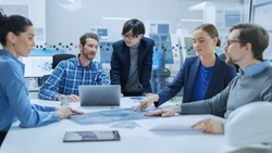 Modern Factory Office Meeting Room: Multi Ethnic and Diverse Team of Engineers, Managers and Investors Talking Sitting at Conference Table, Analyzing Blueprints. High-Tech Manufactory Optimization