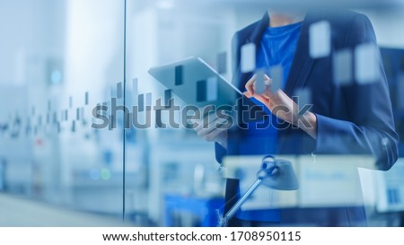 Modern Factory Office: Young and Confident Female Industrial Engineer Standing and Holding Digital Tablet, Using Gestures to Work Efficiently. Focus on Hands and Tablet. Foto stock ©
