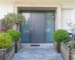 modern family house front entrance stone covered corridor to metal and glass door