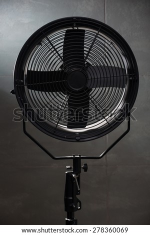 modern fan standing right at the camera. On a black background