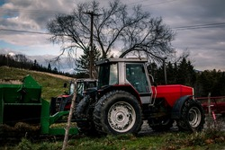 Modern Farm tractors with forage wagon in a farm in the United States. The tractor's trailer or wagon is full of forage crops residue from the fall harvests. A scenery of north American farmland.