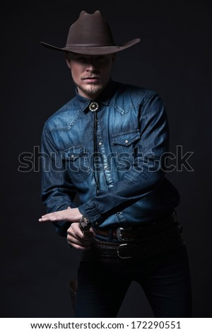 Modern fashion cowboy. Wearing brown hat and blue jeans shirt. Pulling his gun. Blonde hair and beard. Studio shot against black.