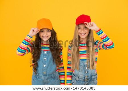 Modern fashion. Kids fashion. Girls long hair wear cap. Cute children wear cap snapback hat. Little girls wearing baseball cap. Matching outfits. Trendy and fancy. Fashion shop. Must have accessory.