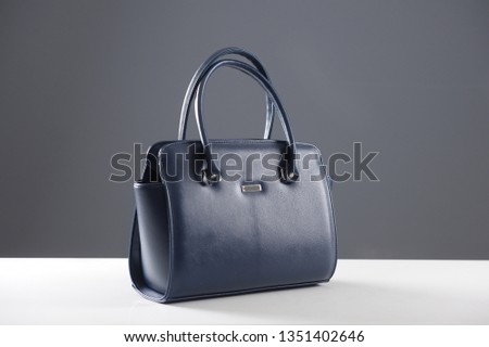 Modern fashionable women handbag. Elegant reptile leather blue women bag on white table and gray background. Beautiful elegance and luxury fashion photo bag  #1351402646