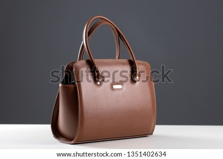Modern fashionable women handbag. Elegant reptile leather light brown women bag on white table and gray background. Beautiful elegance and luxury fashion photo bag  #1351402634