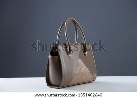 Modern fashionable women handbag. Elegant reptile leather light brown women bag on white table and gray background. Beautiful elegance and luxury fashion photo bag  #1351402640