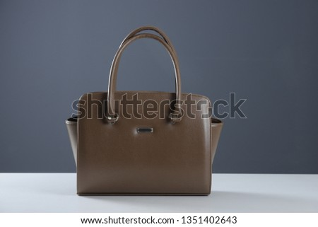 Modern fashionable women handbag. Elegant reptile leather light brown women bag on white table and gray background. Beautiful elegance and luxury fashion photo bag  #1351402643