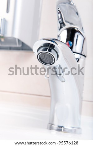Modern faucet closeup with cute water drop