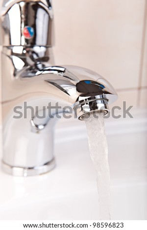 Modern Faucet closeup with streaming water flow