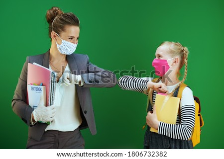 modern female teacher and pupil with masks, yellow backpack and textbook greeted with elbow bump isolated on chalkboard green background.