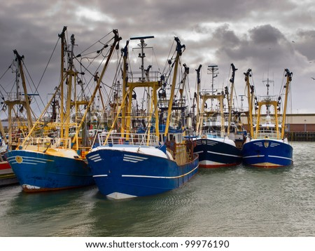 Modern fishing boats under a brooding sky in a dutch fishing harbor