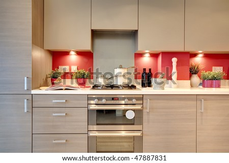 Modern fitted kitchen with utensils and ingredients placed on the worktops